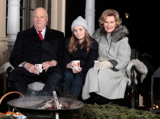 Kong Harald, prinsesse Ingrid Alexandra og dronning Sonja drikker gl¯gg av kopper prinsesse Astrid har malt og spiser pepperkaker utenfor lysthuset pSlottet i forbindelse med julefotografering tirsdag ettermiddag.
